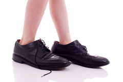 Child wearing adult shoes Royalty Free Stock Photo