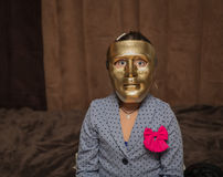 Child wearing on artistic scary bronze color mask and saying trick or treat Stock Photo