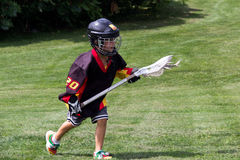 Child wearing black jersey and protective equipment playing lacr Stock Image