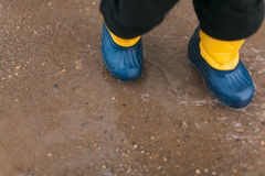 Child wearing boots a puddle. Child wearing blue rain boots a puddle closeup Stock Image