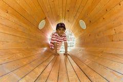 A child inside a wooden loud speaker. Casual portrait.