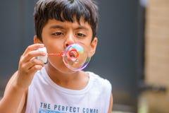 A child blowing soap bubbles; casual portrait