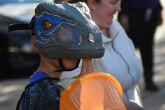 Child wearing a dinosaur mask stock images