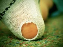 Child wearing dirty socks with holes in the heel. Leg on green carpet Royalty Free Stock Image