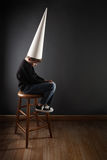 Child wearing a dunce cap. A young boy sits on a stool wearing a Dunce hat stock photography
