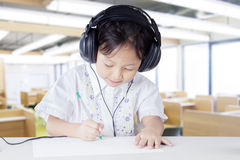 Child wearing earphones in listening lesson. Female elementary school student in the listening lesson and wearing headphones while doing assignment Stock Photography