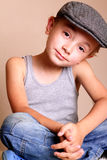 Child wearing Flat Cap. A happy young boy child sitting wearing flat cap and tank shirt Stock Images