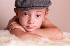 Child wearing Flat Cap. A somber young boy child wearing flat cap Stock Photo