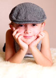 Child wearing Flat Cap. A smiling young boy child wearing flat cap. Shallow depth of field focus on face small little Stock Photo