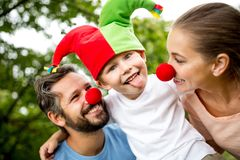 Child wearing fool cap and showing his tongue. With his family stock image