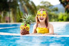 Child with pineapple in swimming pool. Kids swim royalty free stock photography