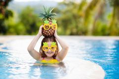 Child with pineapple in swimming pool. Kids swim stock image
