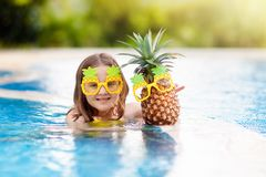 Child with pineapple in swimming pool. Kids swim royalty free stock image