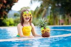 Child with pineapple in swimming pool. Kids swim. Child wearing funny sunglasses with pineapple in swimming pool. Kids swim in tropical resort. Family summer royalty free stock photo