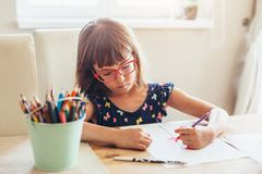 Child in glasses drawing stock photo