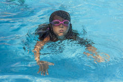 Child wearing goggles, breathing while swimming in the pool. stock photos