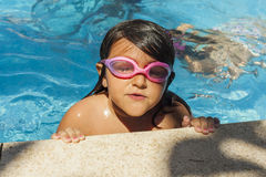 Child wearing goggles and close eyes, getting out of the pool. royalty free stock photos