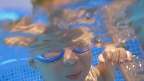 Child wearing goggles diving in the pool. Slow motion close-up shot of a little boy in goggles diving in the swimming pool. Active leisure and recreation stock footage