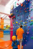 Child wearing a harness is climbing an indoor artificial wall Royalty Free Stock Image
