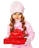 Child wearing in hat and mittens holding red  gift box. Royalty Free Stock Images