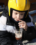 A child wearing a helmet drink hot chocolate Royalty Free Stock Images