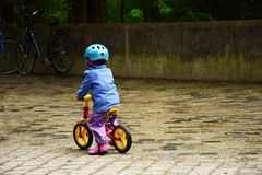 Child wearing a helmet on a running bike in rainy weather stock photography
