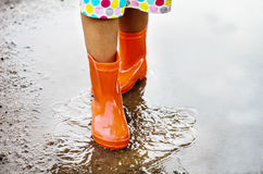 Child wearing orange rain boots. Walking into a puddle. Close up Stock Photo