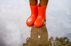 Child wearing orange rain boots stock photography