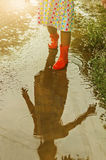 Child wearing orange rain boots walking into a puddle. Close up Royalty Free Stock Images