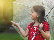 Child wearing polka dots dress under umbrella in rainy day Royalty Free Stock Image