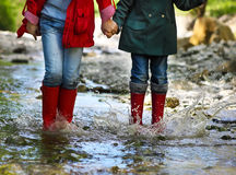 Child wearing rain boots jumping. Close up. Children wearing rain boots jumping into a mountain river. Close up Stock Photography