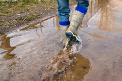 Child wearing rain boots. Jumping into a puddle. Close up Royalty Free Stock Image