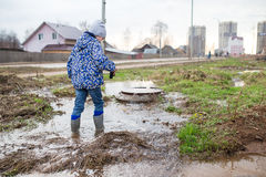 Child wearing rain boots. Jumping into a puddle. Close up Royalty Free Stock Photos