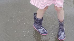 Child wearing rain boots walking into a puddle stock video footage