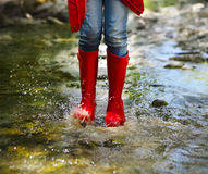 Child wearing red rain boots jumping. Close up. Child wearing red rain boots jumping into a mountain river. Close up Stock Photos