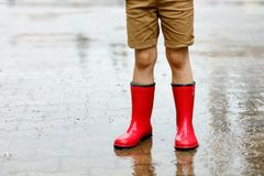 Child wearing red rain boots jumping into a puddle. Close up. Kid having fun with splashing with water. Warm heavy summer rain and happy children Royalty Free Stock Photography