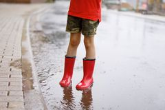 Child wearing red rain boots jumping into a puddle. Close up. Kid having fun with splashing with water. Warm heavy summer rain and happy children Stock Image