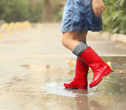 Child wearing red rain boots jumping into a puddle. Close up Royalty Free Stock Images