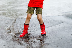 Child wearing red rain boots jumping into a puddle. Close up. Kid having fun with splashing with water Stock Photos
