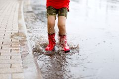 Child wearing red rain boots jumping into a puddle. Close up. Kid having fun with splashing with water. Warm heavy summer rain and happy children Stock Images
