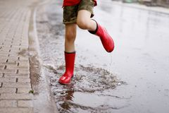 Child wearing red rain boots jumping into a puddle. Close up. Kid having fun with splashing with water. Warm heavy summer rain and happy children Royalty Free Stock Image