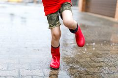 Child wearing red rain boots jumping into a puddle. Close up. Kid having fun with splashing with water. Warm heavy summer rain and happy children Stock Photos