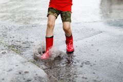 Child wearing red rain boots jumping into a puddle. Close up. Kid having fun with splashing with water. Warm heavy summer rain and happy children Royalty Free Stock Photo