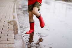 Child wearing red rain boots jumping into a puddle. Close up. Kid having fun with splashing with water. Warm heavy summer rain and happy children Stock Photography