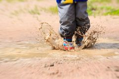 Child wearing red rain boots jumping into a puddle Stock Photos