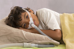 Child wearing a respiratory mask. Child with sleeping apnea and CPAP machine Stock Images
