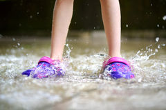 Child wearing rubber shoes jumping into a puddle Stock Image