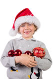 Child wearing a santa hat. And holding baubles Stock Images