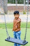 A child pointing to swing in the park; casual portrait