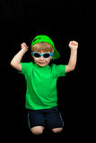 Child wearing summer outfit. Child wearing summer outfit and sunglasses over a black background Royalty Free Stock Image